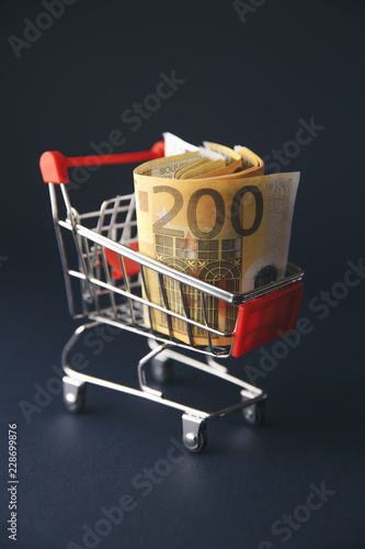 Fotografía  shopping cart filled with european currency notes, isolated on white