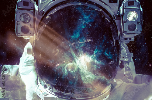 Dark nebula and stars in space, reflection on the spacesuit helmet. Adventure of spaceman. Astronaut in outer space. Elements of this image furnished by NASA.