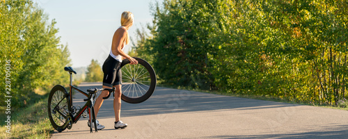 Foto auf Gartenposter Radsport Sexy girl with a road bike and a flat tire looking for help panorama