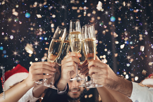 Fototapeta Clinking glasses of champagne in hands at New Year party