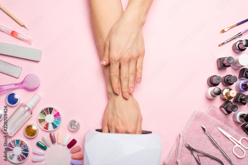 Fototapety, obrazy: Nail care. beautiful women hands making nails painted with pink gentle nail polish on a pink background. Women's hands near a set of professional manicure tools. Beauty care