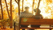 Senior Couple Enjoying Sunset On The Bench In The Autumn Park