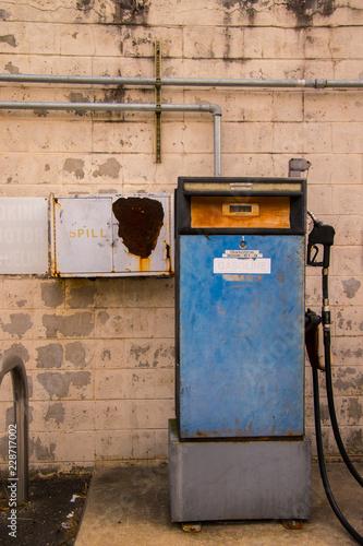 Fotografie, Obraz  Old blue gasoline pump in front of worn white brick wall