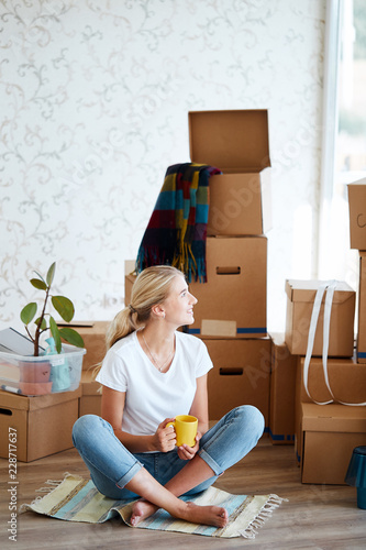 Photo  smiling woman with tea in hand sitting on floor of new apartment, pile of moving