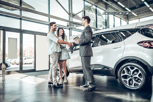 Fototapeta Young couple shaking hands with sales agent after a successful car buying