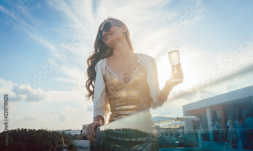 Frau trinkt Glas Sekt auf einer Party im Sommer Wallpaper Mural