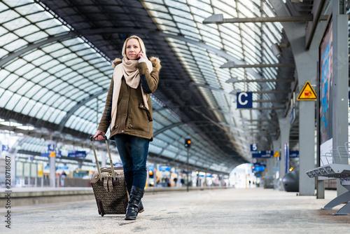 Fotografía  Frau mit Gepäck läuft am Bahnsteig auf Bahnhof entlang