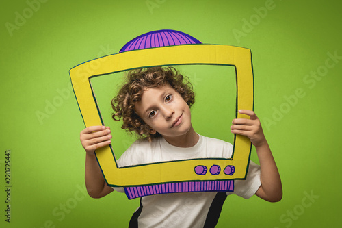 Fotografie, Obraz  A 6-year-old boy plays with a television toy cut out of a piece of cardboard on a green background