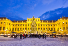 Traditional Christkindlmarkt In Vienna. Christmas Market Scene With Illuminated Schönbrunn Palace And Fairy Lights Decorated Christmas Tree At Dusk.