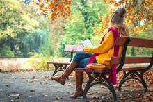Woman Sitting On Bench And Reading Book. Autumn At Public Park. Woman Wearing Sweater, Jeans And Leather Boots.