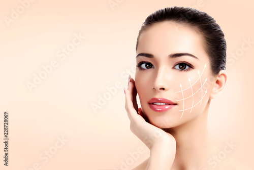 Poster Spa Closeup shot of female pretty face with white arrows on skin for cosmetic medical procedures, pastel background. Skin care concept