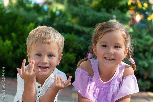Fotografia, Obraz  Waist up portrait of two cute little smiling children, boy and girl, brother and