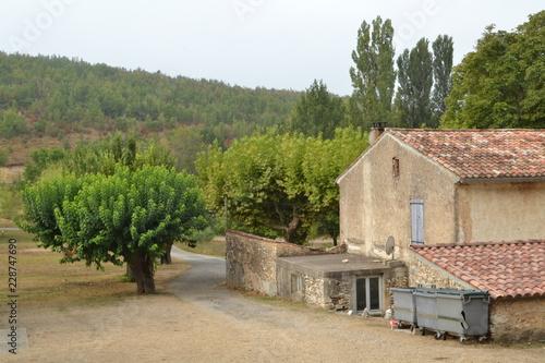 Photo zijkant van boerderij in de Provence met schuren, woonhuis, oprijlaan en vuilnis