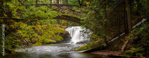 Waterfall in Whatcom Falls Park. A beautiful waterfall runs through this 241-acre park located in a rainforest environment with fir, maple and cedar trees. Autumn has arrived with colorful leaves.