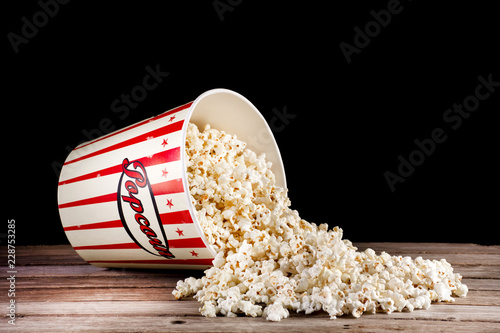 Fotografering  Spilled box with popcorn on retro wooden desk and black background
