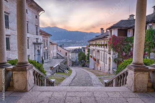 Fototapeta Beautiful scenic alley with historic and traditional houses and cobbled street at sunset