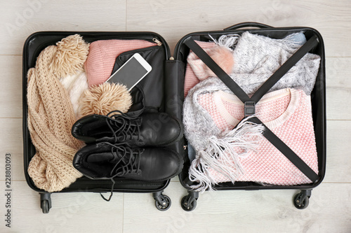 Packed suitcase with warm clothes and smartphone on wooden background, top view. Space for text