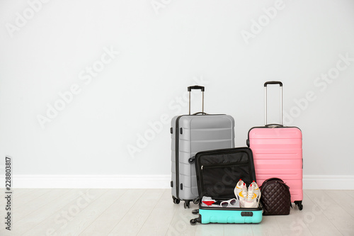 Modern suitcases on floor near light wall. Space for text