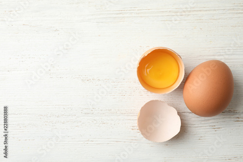 Fotografía Raw chicken eggs on wooden background, top view. Space for text