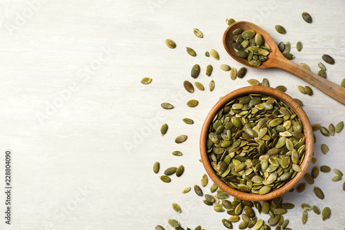 Shelled raw pumpkin seeds on light background, top view. Space for text