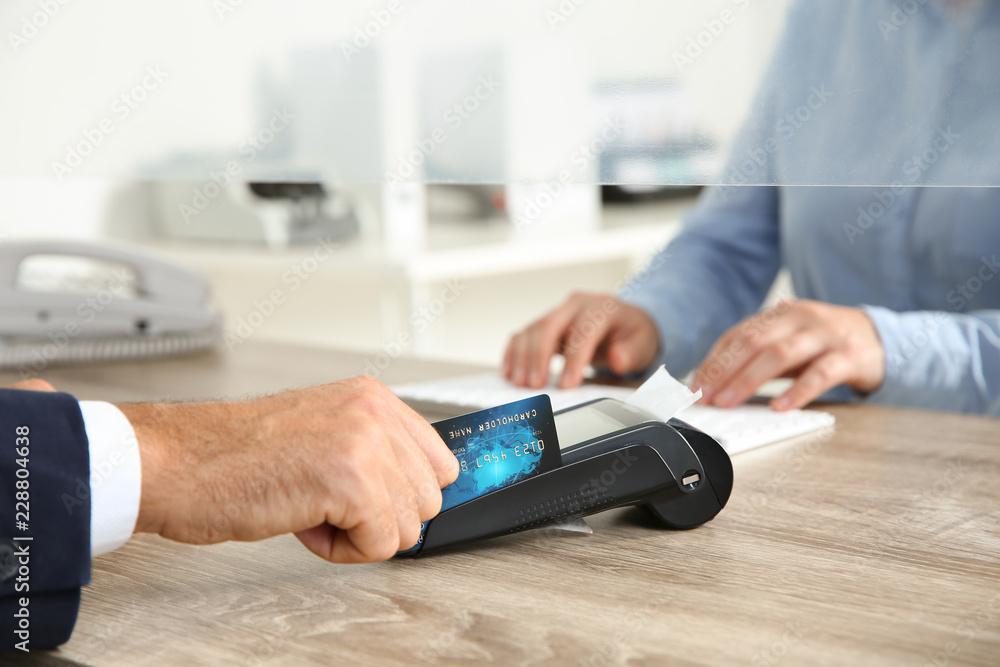 Fototapeta Man using bank terminal for credit card payment at cash department window, closeup