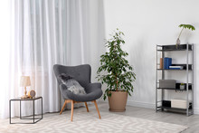 Stylish Room Interior With Armchair And Potted Ficus