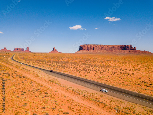 Fototapeta July 30, 2018. Monument Valley National Park, Utah, USA. White Ford Mustang parked by the side of the road at Monument Valley National Park with an amazing view on the infinite road through the desert obraz
