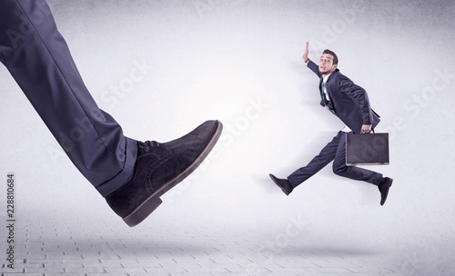 Fotografie, Obraz Small young businessman kicked out by a big black shoe