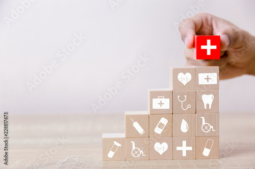 Fotografie, Obraz  Health Insurance Concept,hand arranging wood block stacking with icon healthcare medical