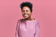 Portrait of overjoyed happiness African American female, widely smiled and close eyes, celebrates her success, poses against pink background. People, happiness, success concept