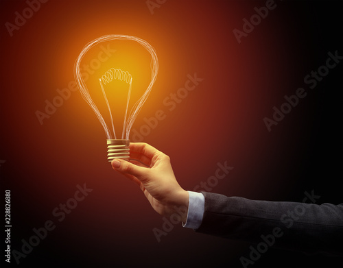 Fototapety, obrazy: Hand holding light bulb on dark background. New idea concept