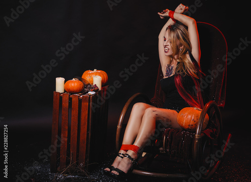 Photo  Halloween concept, girl vampire with red eyes red lips sit on rocking chair with pumpkins around
