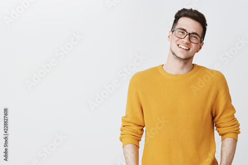 Fotografía Waist-up shot of happy and delighted handsome young man in glasses and yellow sw