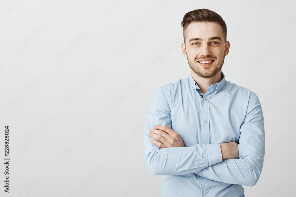 Fototapeta Confident and friendly handsome ambitious man with bristle in blue collar shirt holding hands crossed on chest in self-assured pose smiling joyfully intirigued to listen new idea how gain clients