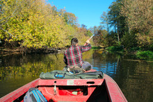 Fisherman With Paddle Floats Down River With Dense Vegetation Along Banks
