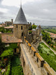 Carcassonne defensive medieval wall with cityscape and clouds background, Languedoc, France