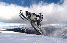 RIDER JUMPING WITH SNOWMOBILE BETWEEN CLOUDS