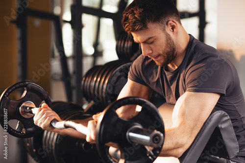 Leinwand Poster Handsome man doing biceps lifting barbell on bench in a gym