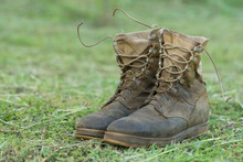 Close Up Front View Of A Pair Of Muddy Boots Isolated On Green Grass Ground.