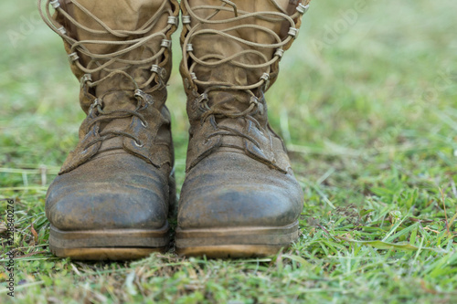 Fotografía  Close up front view of a pair of muddy boots isolated on green grass ground