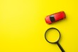 Leinwandbild Motiv Red car and magnifying glass on yellow background with copy space. Auto insurance business concept. Cover life, property damage and injury of third party