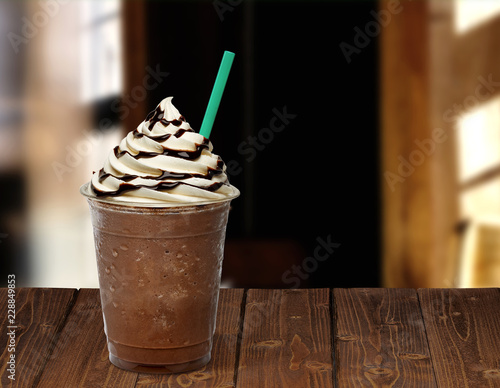 Obraz na plátne Frappuccino in takeaway cup on wooden table isolated on cafe background
