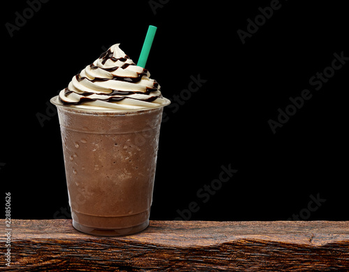 Fotografie, Obraz  Frappuccino in takeaway cup on wooden table isolated on cafe background