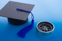 Graduation Cap And Compass On Blue Background. Direction Of Education Reform Due To Digital Disruption Or Innovation Technology Concept. Online Education, E-learning And Certification Is Next Future.