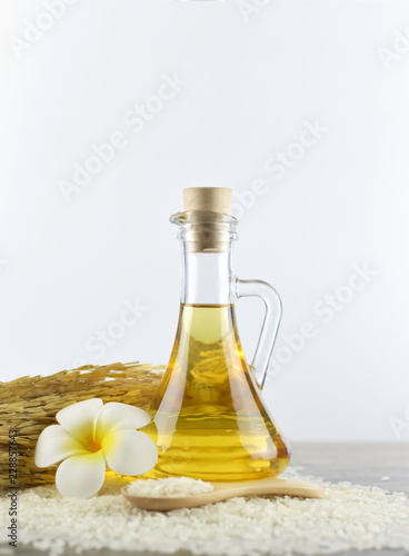 Obraz na plátne  Rice bran oil (vegetable oil) in a glass jar with cover, uncooked jasmine rice i
