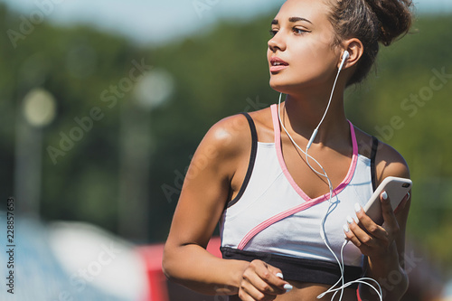 Woman running and listening to music at the sports stadium. Close up - 228857653