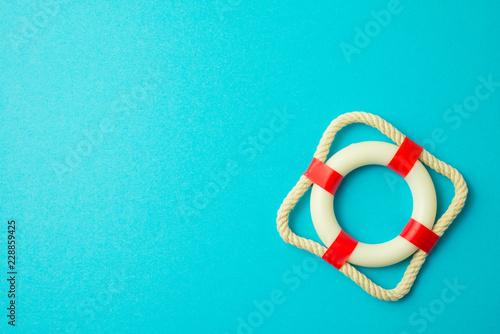 Fotografie, Obraz Flat lay of first aid white - red lifebuoy, lifesaver or lifebelt on blue background