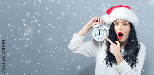 Fotografia, Obraz  Young woman holding a clock showing nearly 12 on a gray background
