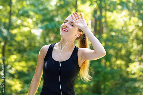 Foto Athletic woman tired from a workout on a bright summer day in the forest