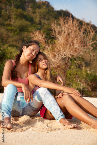 Sleepy dreamy mixed race women sit on sandy beach, demonstare friendly relationships and truthful feelings, have homosexual relations, rest in exotic place. Its time for relax. Summer time concept